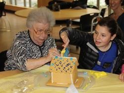 Older woman sits with a young girl as they put the finishing touches on a gingerbread house at Simon C. Fireman Community