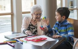 Older woman sits at a table with a young boy as they play with colorful finger puppets.