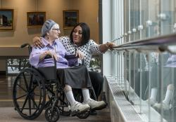 A Patient Care Associate at HRC-Boston talk with a patient in a wheelchair in the Daniels Art Gallery.