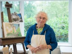 An Orchard Cove resident takes a break from painting in a sunny art studio.
