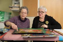 Two female residents peruse art work