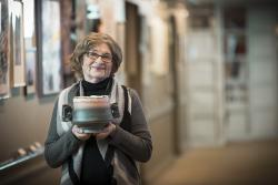 An older woman in gray sweater standing in a hallway gallery at Orchard Cove holds a ceramic pot she has made.