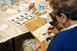 An older woman in a blue shirt and brightly flowered apron paints a yellow brush stroke as she begins a watercolor in an art workshop.