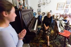 Young girl stands in foreground as an older woman sits at a piano in her apartment as part of a program to bring visitors to seniors in their homes.