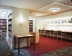 Book-filled shelves and plenty of work space line the CCB library.