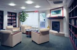 Bookshelves lined with books and sun-filled windows create a comfortable sitting area for CCB residents.