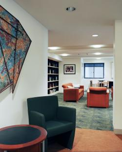 The entrance to a sitting area, with comfortable chairs and book-lined shelves.