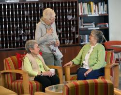 Three woman enjoy a conversation in one of the many sitting areas at Center Communities of Brookline.