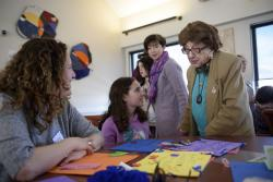 A woman and her younger daughter sit at a table that is covered with multicolor construction paper and craft supplies. They are smiling at an older woman who has stopped to talk to them.