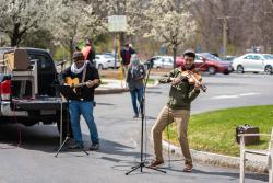 Two musicians perform outside of Simon C. Fireman Community during pandemic