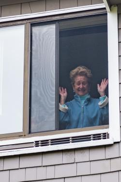 A resident of Simon C. Fireman Community looks out her window and waves during an outside concert