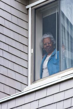 A resident of Simon C. Fireman Community smiles and looks out her window during an outside concert