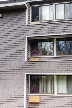 Residents on three floors of Simon C. Fireman Community look out their windows and listen to an outside concert