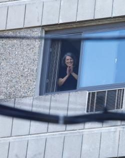 A smiling CCB resident looks out a window and listens to an outside concert.