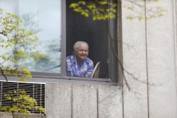 A CCB resident looks out a window and listens to an outside concert.