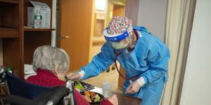 A NewBridge employee wears PPE while checking a resident's vitals.