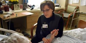 Rabbi Sara Paasche-Orlow  sits in a chair and holds a patients hand while talking to her