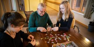 A male resident sits and puts together a puzzle with two young female volunteers