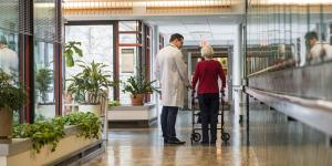 A male doctor talks with older woman using walker in Hebrew Rehabilitation Center hallway
