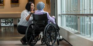 A HSL employee bends over to talk to a patient in a wheelchair.