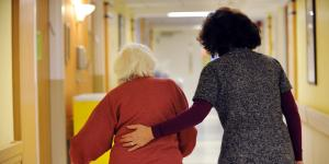 A woman guides a resident using a walker down a hallway.
