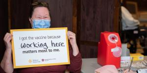 "A Hebrew SeniorLife employee sits in a chair, wearing a surgical mask with a sign that says ""I got the vaccine because working here matters most to me."" The words ""working here"" are handwritten."