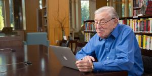 An older man smiles while using a laptop.