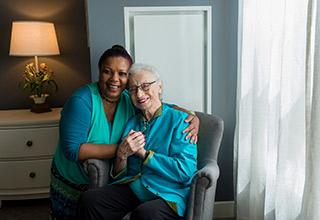 A caretaker hugs an older woman sitting in a chair as they both smile.