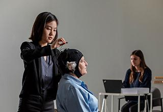 An elder woman participates in Marcus Institute research by getting her brain stimulated