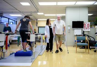 Older patients participate in rehabilitation therapy sessions, with therapists.