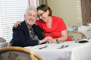 A male senior living resident and his adult daughter embrace in a hug at a dining table.