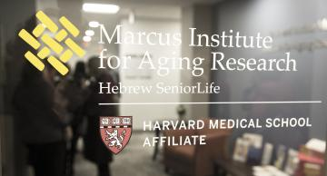 Glass window with white logo on it saying Marcus Institute for Aging Research.