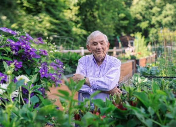 A man standing in the middle of a community garden at NewBridge on the Charles. He is looking at the camera, arms crossed, with a slight smile.