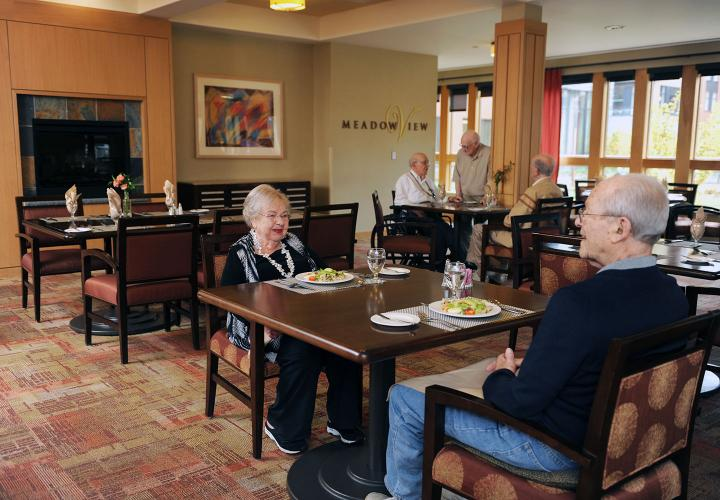 Several assisted living residents enjoy lunch in MeadowView, our restaurant offering three meals daily at NewBridge on the Charles.