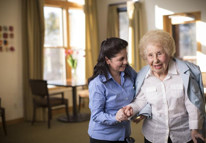 An assisted living resident at NewBridge on the Charles receives help with the tasks of daily living in her bright apartment.