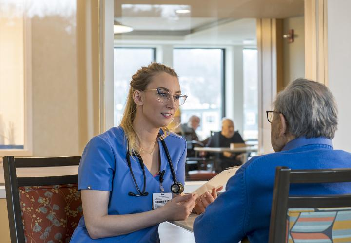 Caregiver wearing blue talking to patient in long-term chronic care sitting down at table