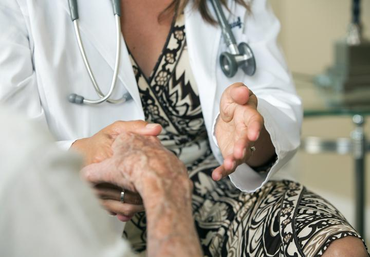 Close up of a doctor holding the hand of a patient.