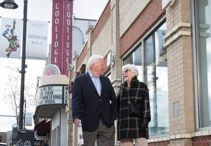 An older couple takes a fall stroll on Beacon Street, passing the iconic Coolidge Corner theatre.