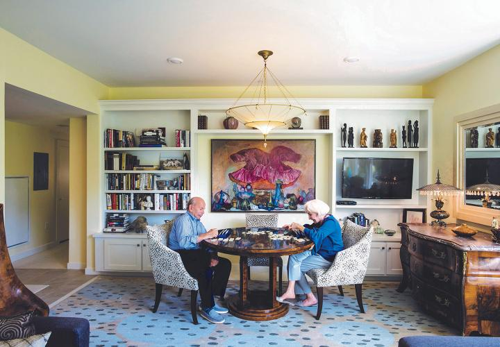 A couple enjoy a game in the library of their villa residence at NewBridge on the Charles.