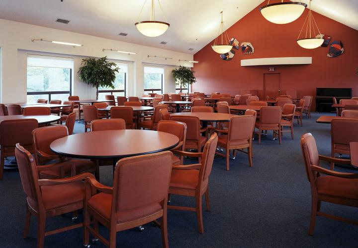 Dining room at 100 Centre Street, filled with red chairs and tables and low-hanging lights