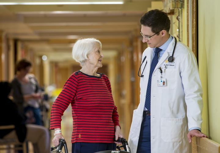 A doctor wearing a white coat leans against the wall in a hallway, talking to an older patient standing next to him.