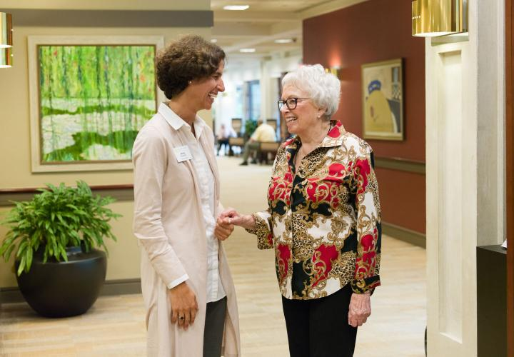 Orchard Cove's executive director chats with older woman in the Orchard Cove main lobby.