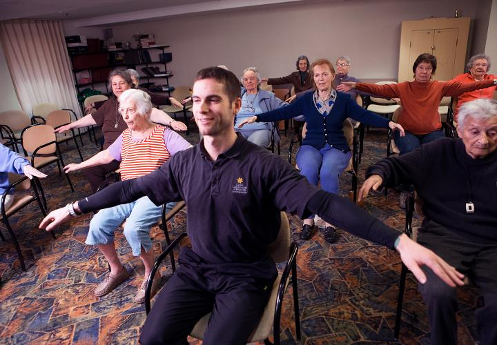 Fitness instructor with residents doing exercises