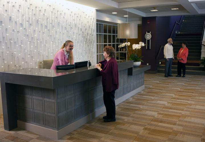 Front-desk receptionist helps a resident requesting a service.