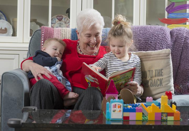 Happy grandmother, an HSL resident, reading to grandson and granddaughter