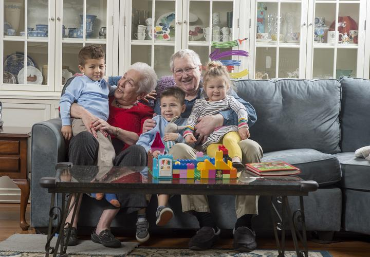 Smiling grandmother and grandfather with three grandchildren, two boys and one girl, seated on sofa