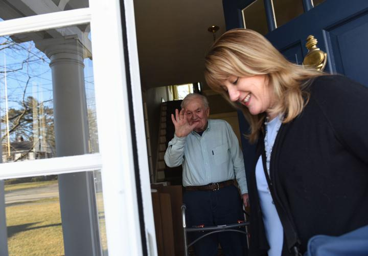 Older man with walker stands at doorway of his home as he waves goodbye to his home health nurse