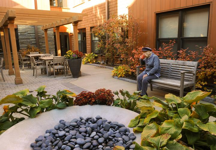 A resident of memory care assisted living at NewBridge on the Charles enjoys a quiet moment in one of two secure outdoor courtyards.