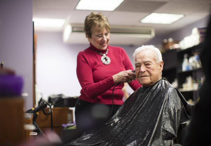 An older man is seated in a barber's chair wearing a cape. A woman stands behind him, cutting his hair.