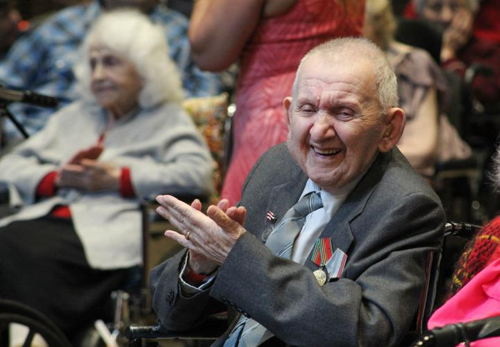 An older Russian man sits clapping and smiling at Hebrew Rehabilitation Center during a Victory Day celebration. He is wearing medals that show he is a veteran.
